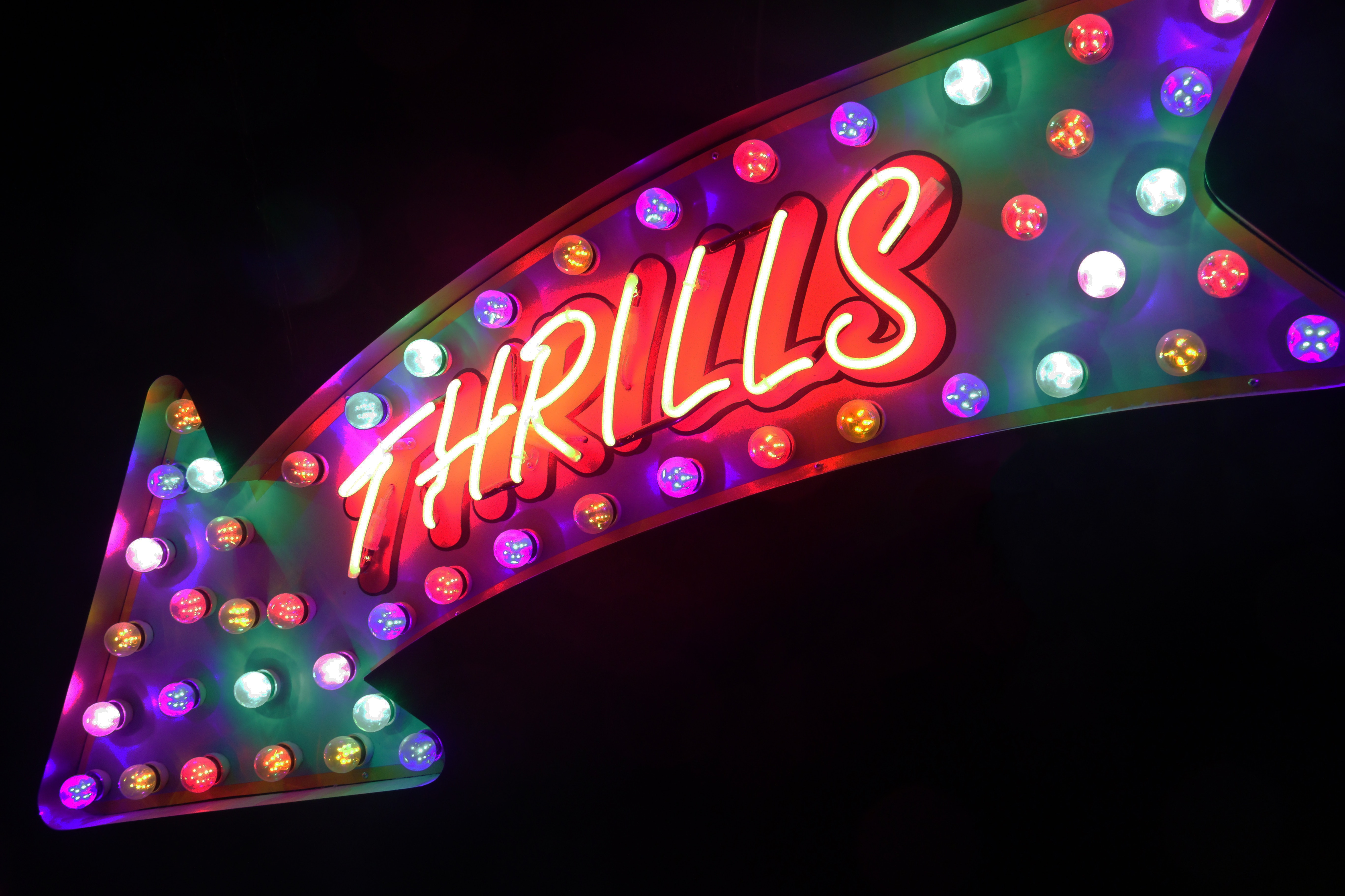 Large lighted arrow with multi colors that says Thrills!