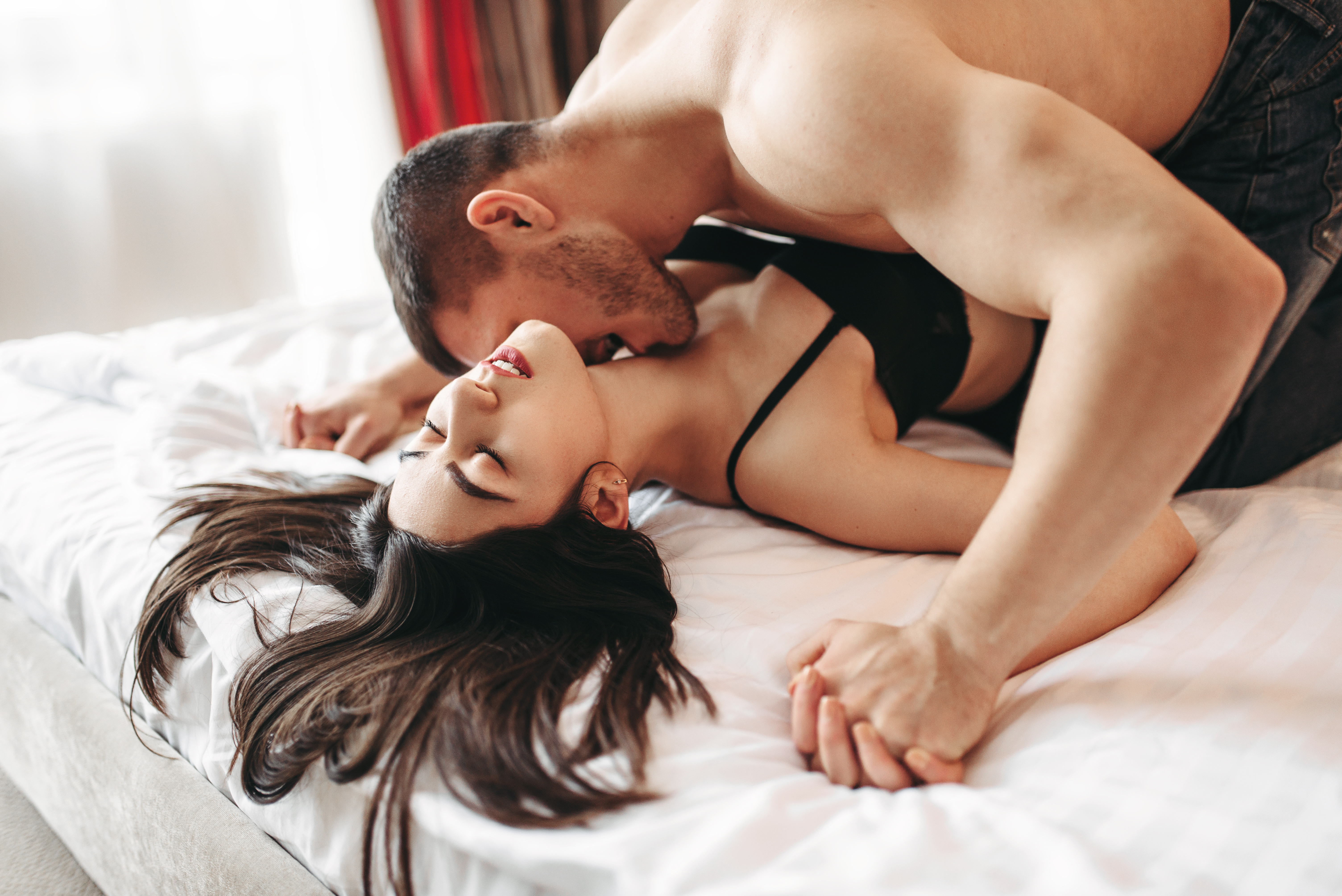 A couple on a bed together half naked and the man is kissing the woman necking she is looking at him with passion