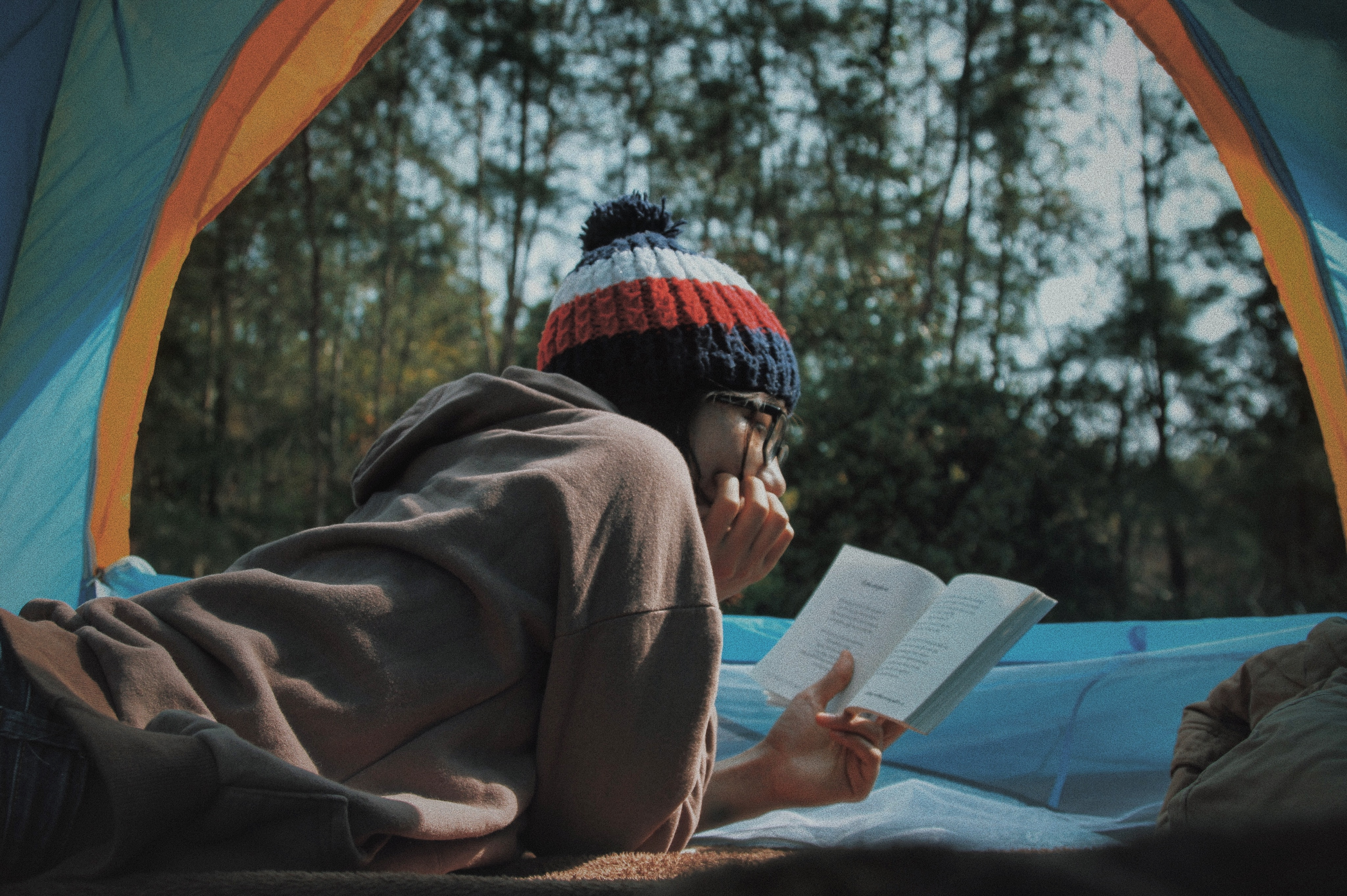 Young woman reading a book in a tent outside