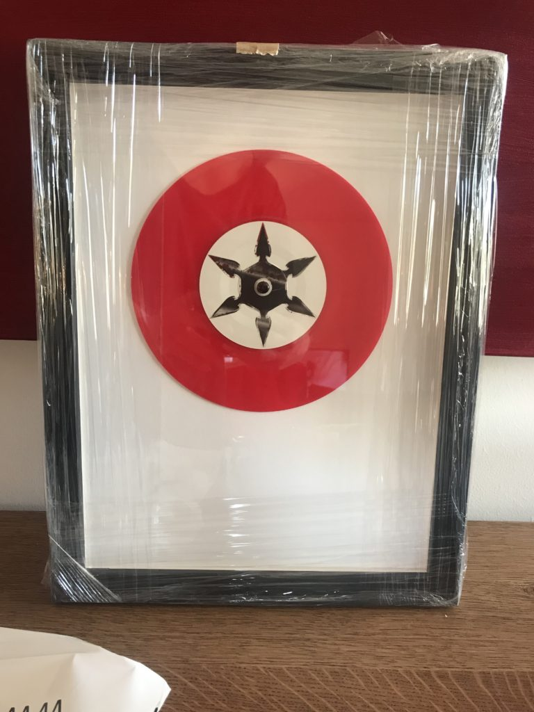 Small 45 record in red with black center framed in modern black wooden frame