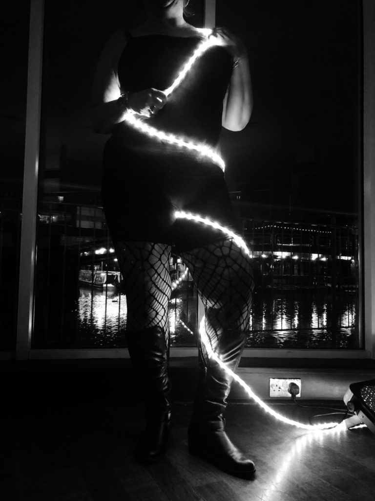 sexy black and white photo of me in fishnet tights, black panties and tank awith rope light stung all over me