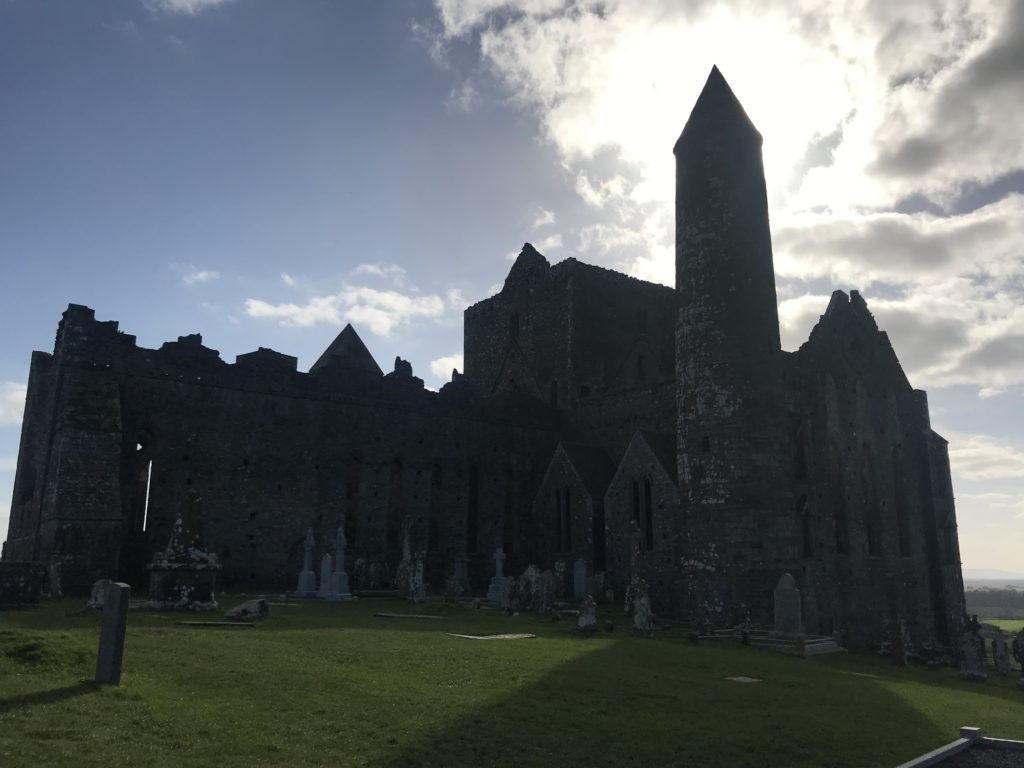 Silhouette shot of the Rock of Cashel with the sun shining behind it