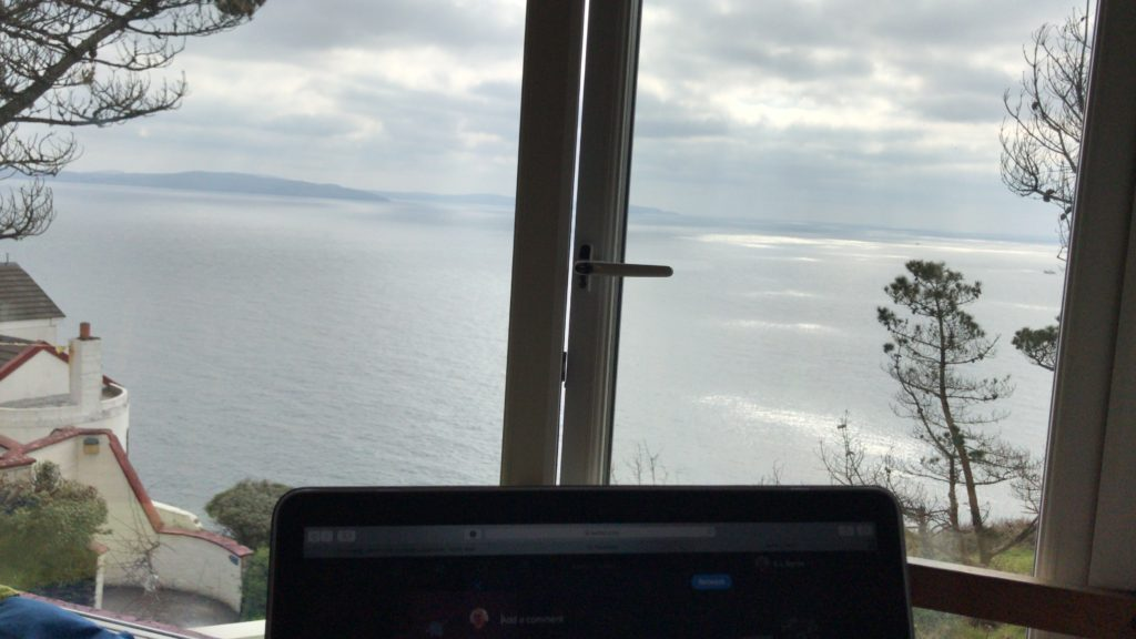View of my laptop and some writing overlooking the ocean and cliffs in Cork Ireland