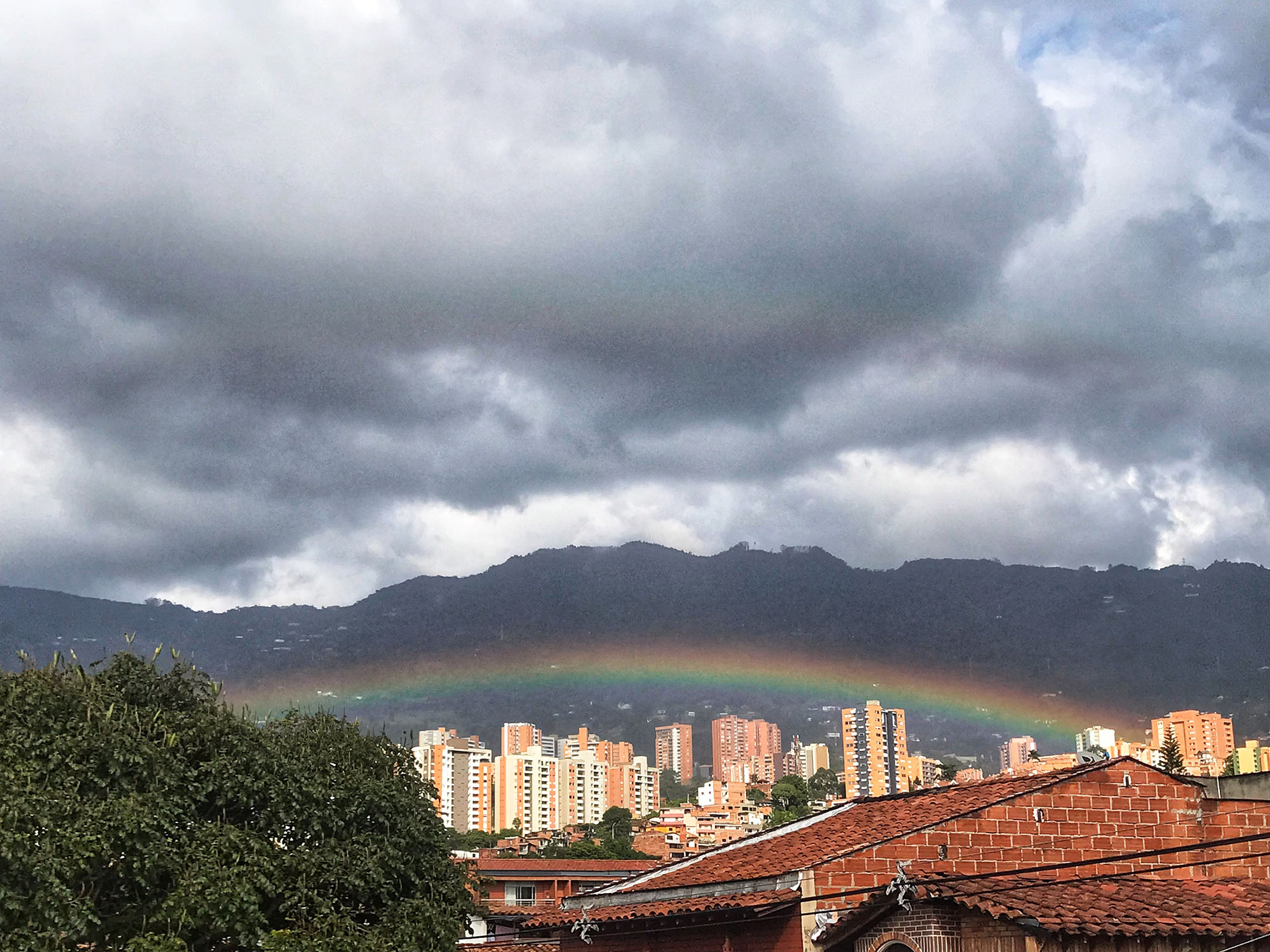 Rainbow over rooftops and below the mountain in Medellin