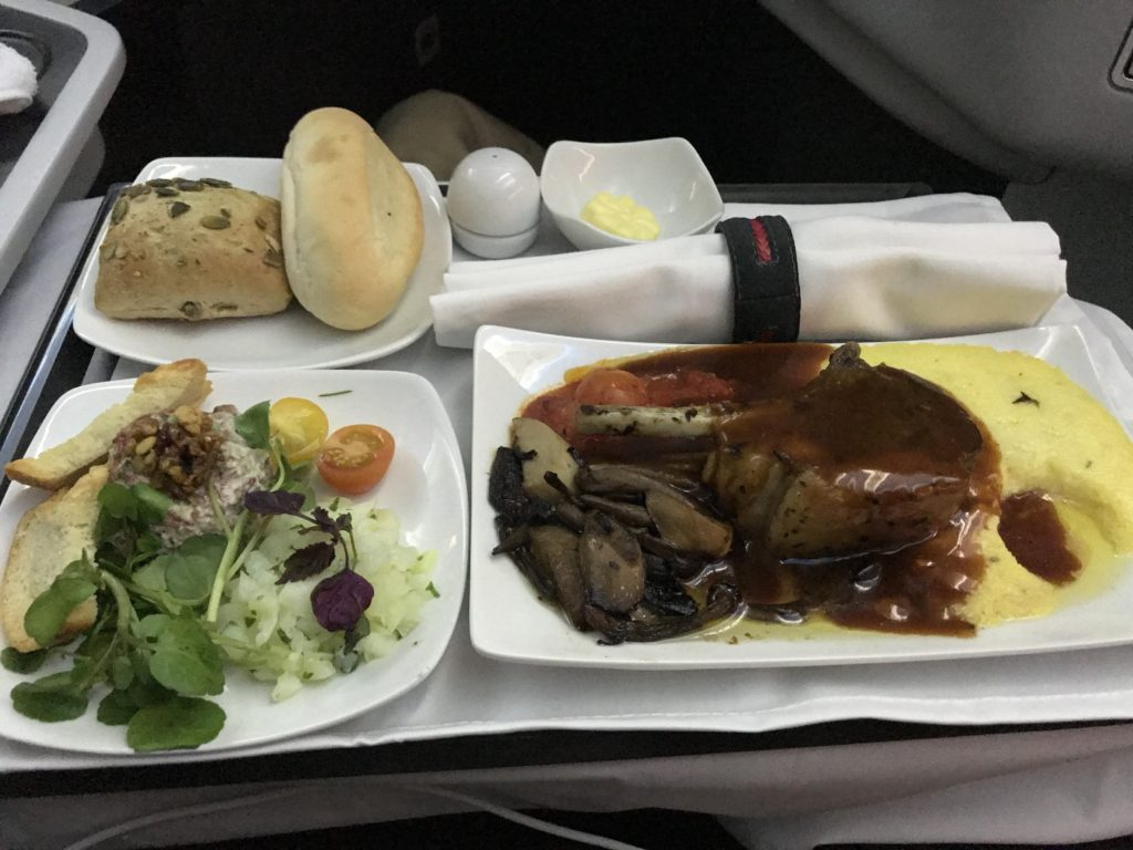 Business class dinner on a plane with cloth napkins and tablecloth