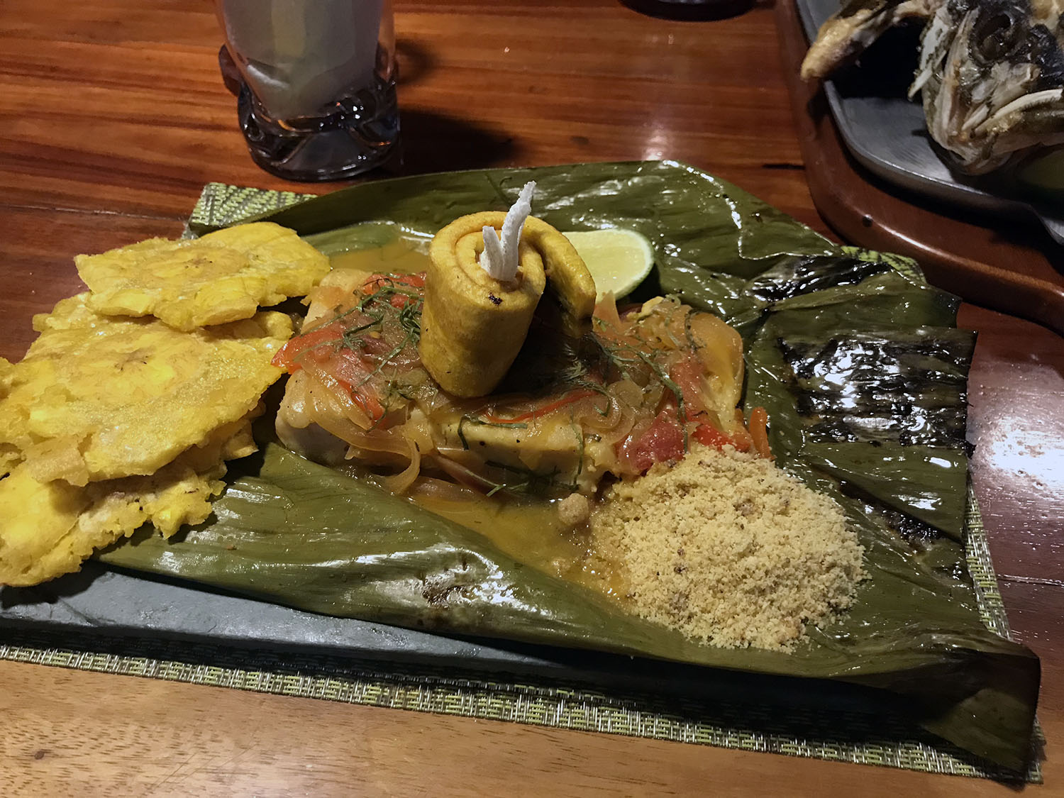 Delicious fish served a banana leaf, with a patacone and sauce on the dish