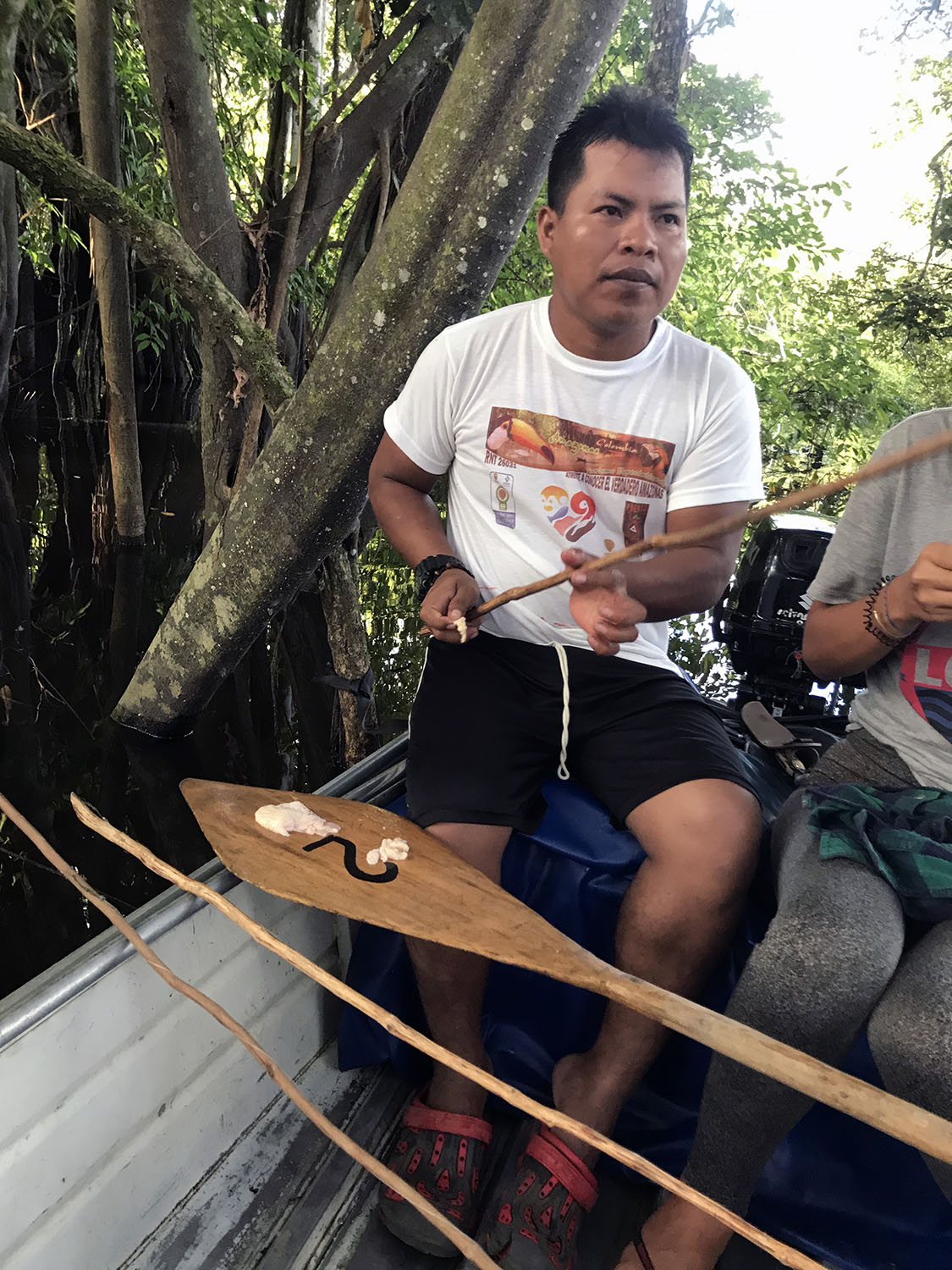 Local guide using fresh fish to bait traditional fishing poles to fish for piraña