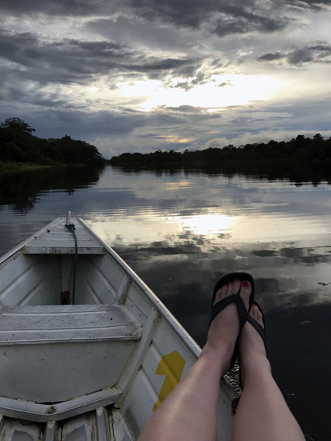 Amazon river reflecting the dusky sky with boat in foreground and feet relaxing off the side