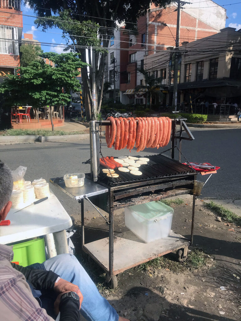 Cart with sausages hanging from it on the street corner