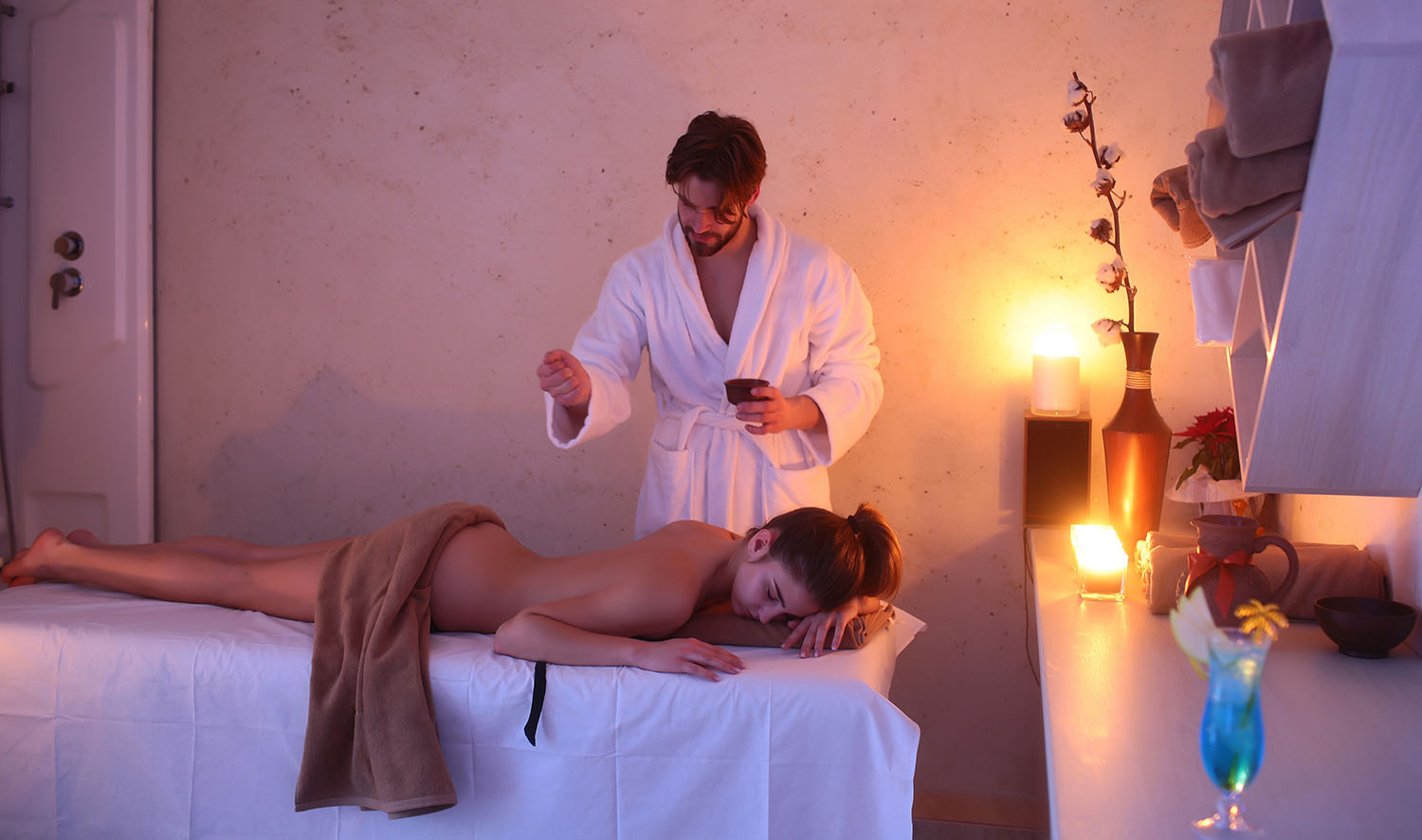 pretty woman or girl with sexy body and handsome bearded man of masseur therapist in white terry bathrobe makes massage in beauty spa salon with candles and cocktail glass